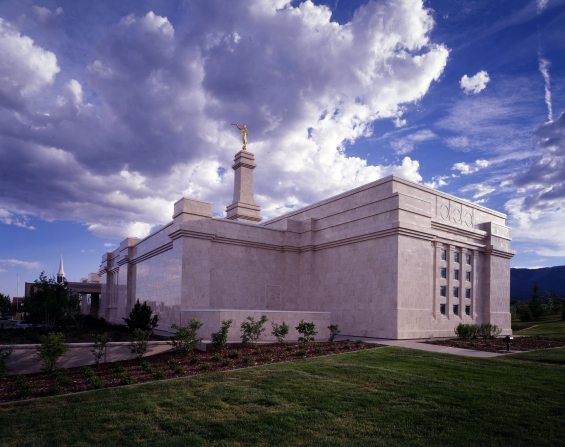 The side of the Monticello Utah Temple amid green grass and plants on a sunny day, with a partly cloudy sky.