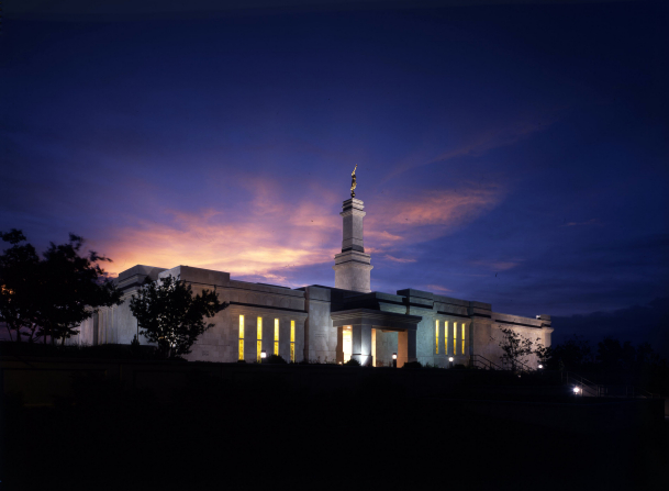 The Monticello Utah Temple is lit up with exterior lights in the evening, with scenery of silhouetted trees against a sunset sky.