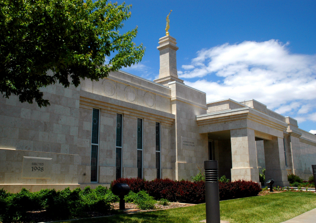 A close-up side view of the entrance to the Monticello Utah Temple, including scenery of green grass and plants, with a tree's leafy branches showing on the left side.