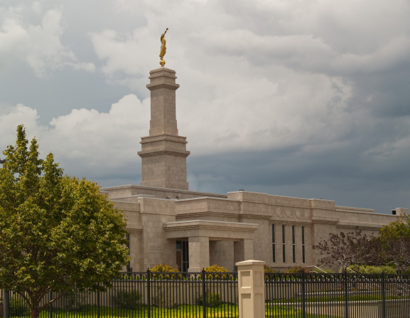 A front view of the Monticello Utah Temple entrance, fences, and green grass and trees, with a stormy sky.