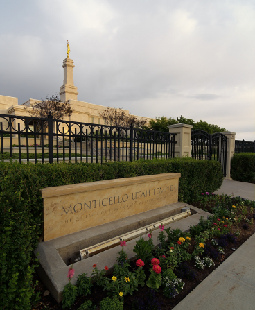 The name sign of the Monticello Utah Temple, with flowers and plants in front of the temple fence.