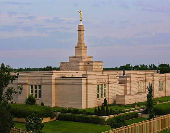 The Montreal Quebec Temple amid green grass, with the temple's fence seen in the bottom right corner.