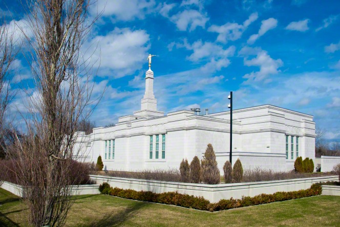 The Montreal Quebec Temple and grounds on a sunny day, with some clouds in the bright blue sky overhead.