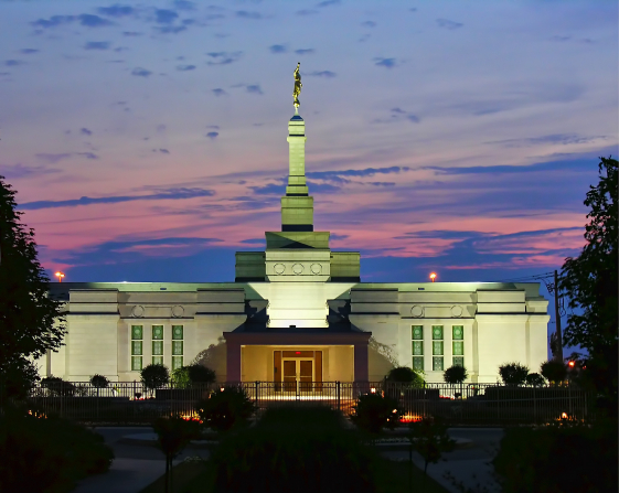 The front entrance to the Montreal Quebec Temple, with the lights on in the evening and the pink and purple evening sky seen overhead.
