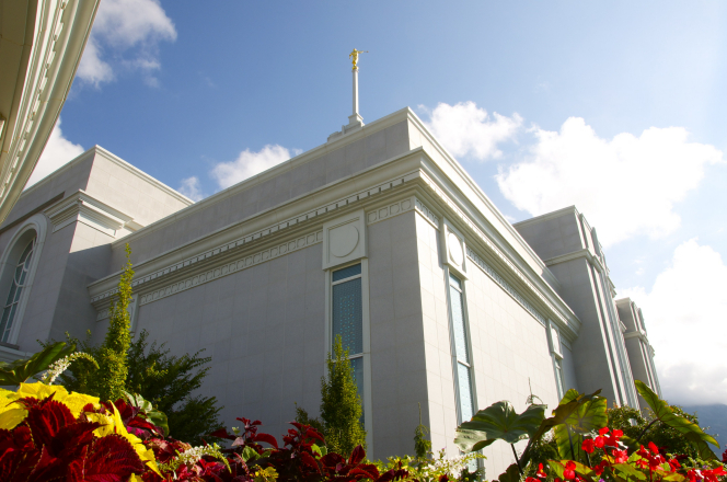 A view from one of the corners of the Mount Timpanogos Utah Temple, looking up toward the spire, with colorful vegetation growing in the foreground.