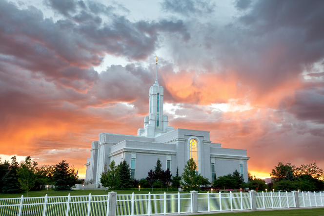 A front side view of the Mount Timpanogos Utah Temple during sunset, with pink and orange clouds over the temple's spire.