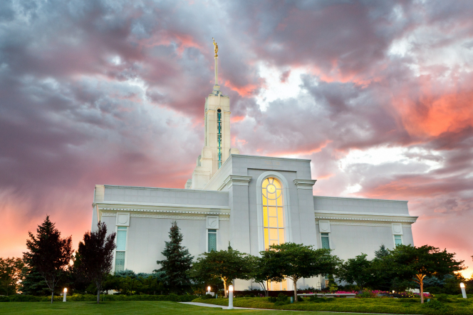A view of the Mount Timpanogos Utah Temple reflecting the colors of the sunset, with the lights on inside and outside of the temple.