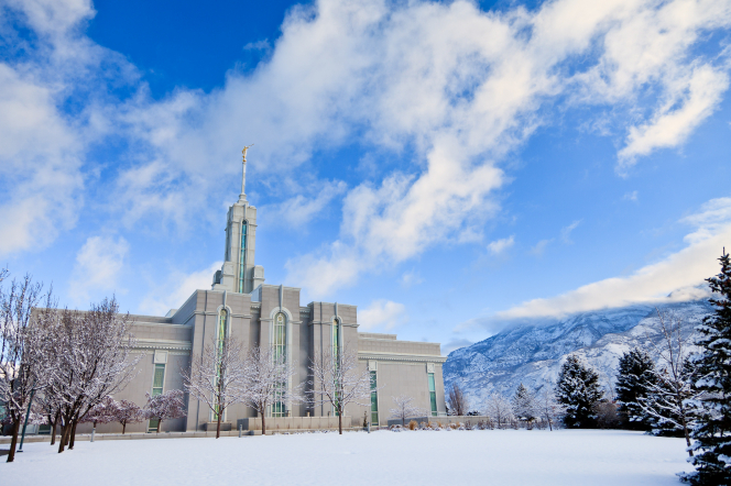 A view of the Mount Timpanogos Utah Temple and grounds covered in snow on a winter day, with fluffy white clouds overhead.