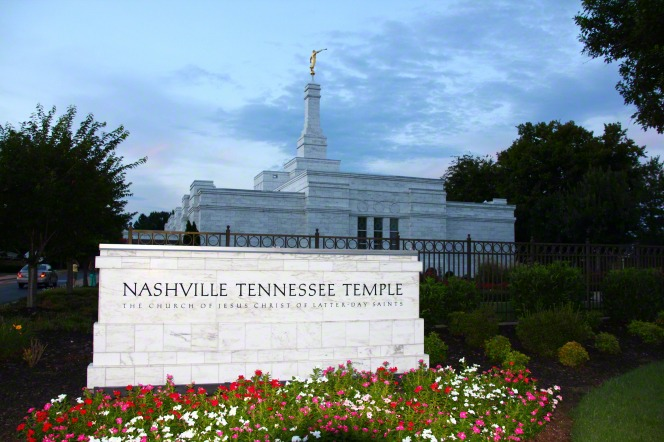 The sign in front of the Nashville Tennessee Temple illuminated in the evening, with the temple in the background.