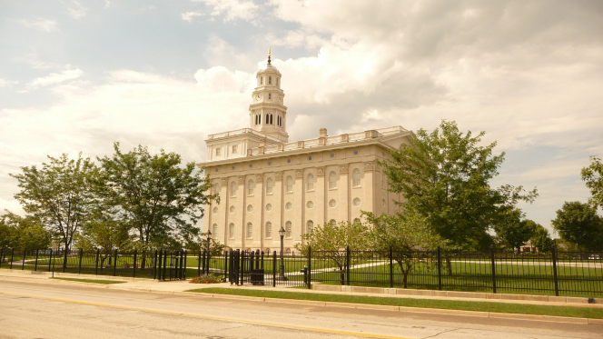 A side view of the Nauvoo Illinois Temple and grounds on a sunny day, with the temple's black fence surrounding the perimeter of the grounds.