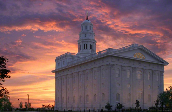 A back and side view of the Nauvoo Illinois Temple in the evening, with an orange and pink sunset filling the sky overhead.