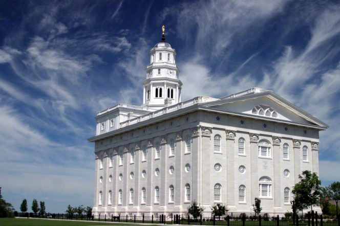 The back and side of the Nauvoo Illinois Temple on a bright day, with a blue sky and thin white clouds overhead.