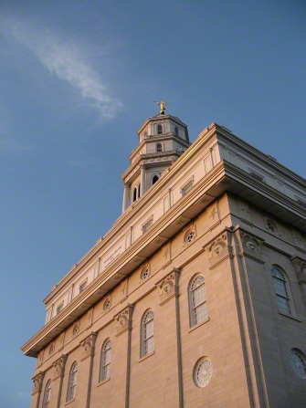 The front of the Nauvoo Illinois Temple from below, with the spire against a blue sky.