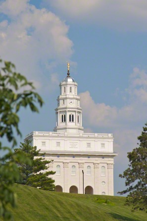 The front of the Nauvoo Illinois Temple from afar, over the top of a green hill, with the green leaves of nearby trees in the foreground on the sides.