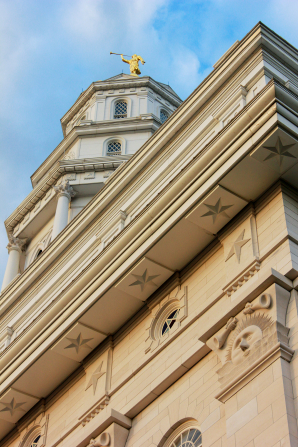 A detail of the sunstones and stars on the outside of the Nauvoo Illinois Temple, with the spire seen beyond them.