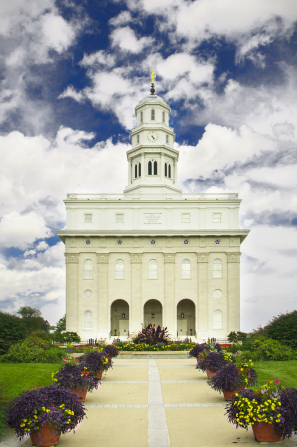 A portrait view of the front of the Nauvoo Illinois Temple, with a flower-lined path leading toward the temple's entrance.