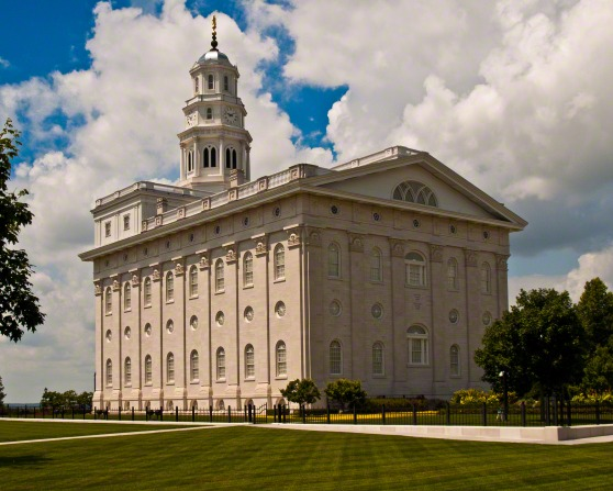 The back and side of the Nauvoo Illinois Temple, with a blue sky seen through the clouds and well-manicured green lawns in the foreground.