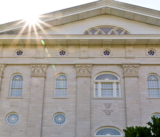 "A detail of the Nauvoo Illinois Temple, with sunshine over the roof and the words ""Holiness to the Lord: The House of the Lord"" engraved on the building."