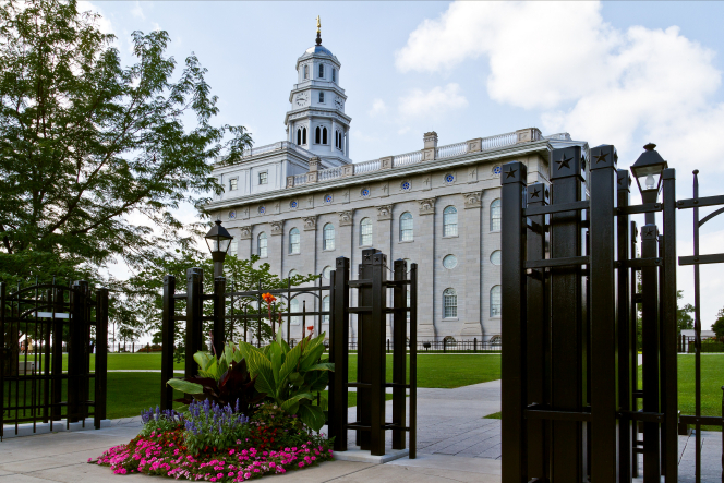 A side view of the Nauvoo Illinois Temple, seen through the rungs and gates of a black fence that surrounds the temple grounds.