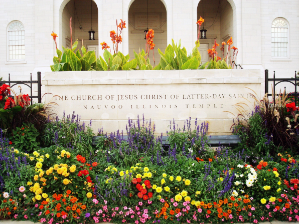 The stone sign outside of the Nauvoo Illinois Temple, surrounded by colorful flowers, with some of the temple's arches seen in the distance.