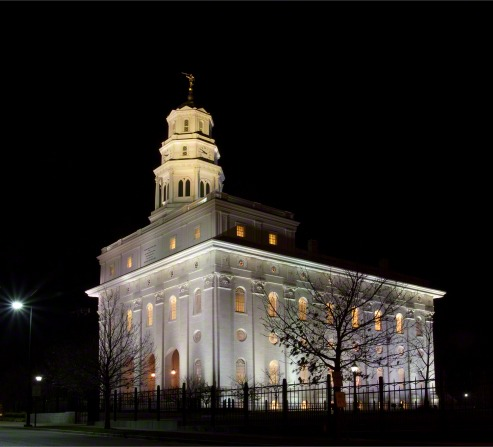 A front side view of the Nauvoo Illinois Temple on a dark night, with dark, bare trees silhouetted in the foreground.