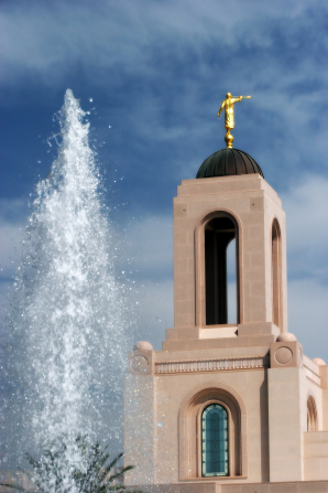 The spire on the Newport Beach California Temple, with the water from a fountain on the grounds showing on the left side.