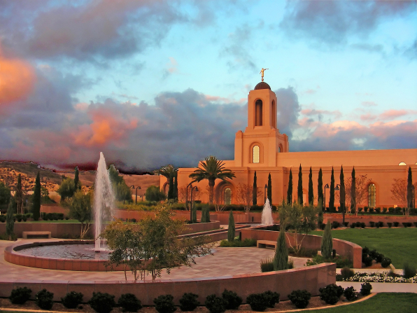 A large water fountain on the grounds of the Newport Beach California Temple at sunset, with the temple seen behind it.