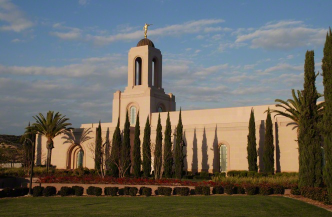 A side view of the Newport Beach California Temple in the sunset, with manicured bushes and trees growing on the temple grounds.