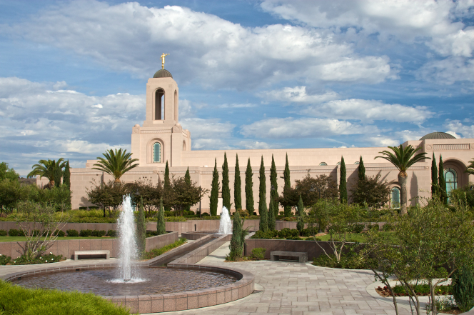 The fountains on the grounds of the Newport Beach California Temple, with the temple seen in the background beyond green trees.