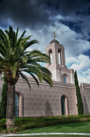 The Newport Beach California Temple and spire, with darkening clouds overhead and a palm tree growing near the temple.