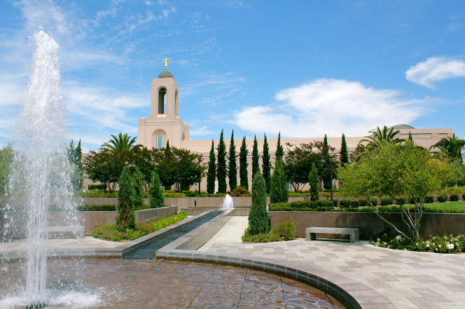 The water from a fountain on the grounds of the Newport Beach California Temple, with the temple and temple's trees seen behind it.
