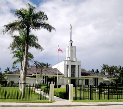 The Nuku'alofa Tonga Temple seen beyond the temple's fence, with the gate open to the path that leads to the entrance.