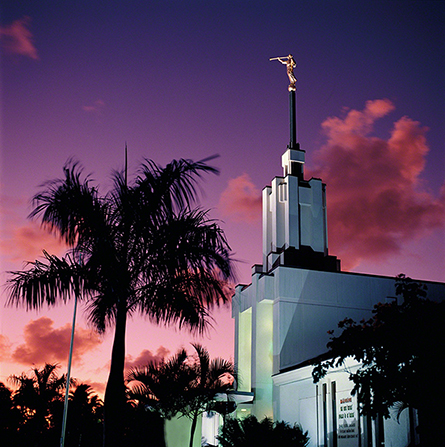 The front of the Nuku'alofa Tonga Temple in the evening, with a pink and purple sunset overhead and the shadow of a palm tree in the foreground.
