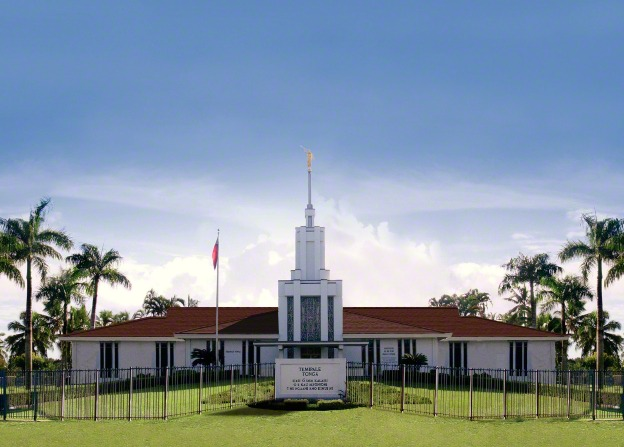 The front of the Nuku'alofa Tonga Temple, with the temple's sign seen near the black fence that surrounds the grounds.