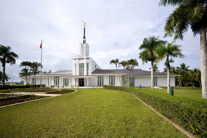 The Nuku'alofa Tonga Temple on a sunny day, with a large green lawn in front.