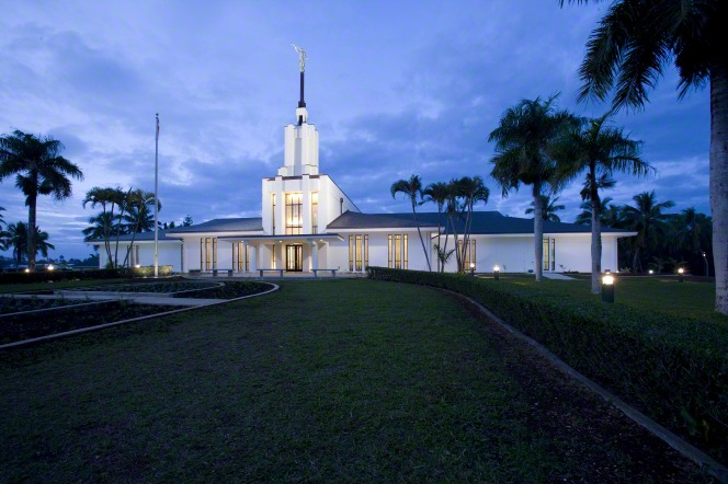The Nuku'alofa Tonga Temple, with the lights on in the evening and a green lawn in front of the temple.