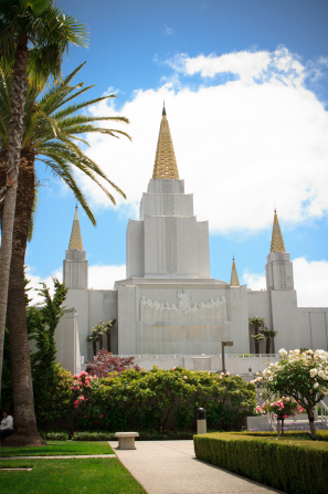 The front of the Oakland California Temple on a sunny day, with a bright blue sky overhead and vegetation growing on the temple grounds.