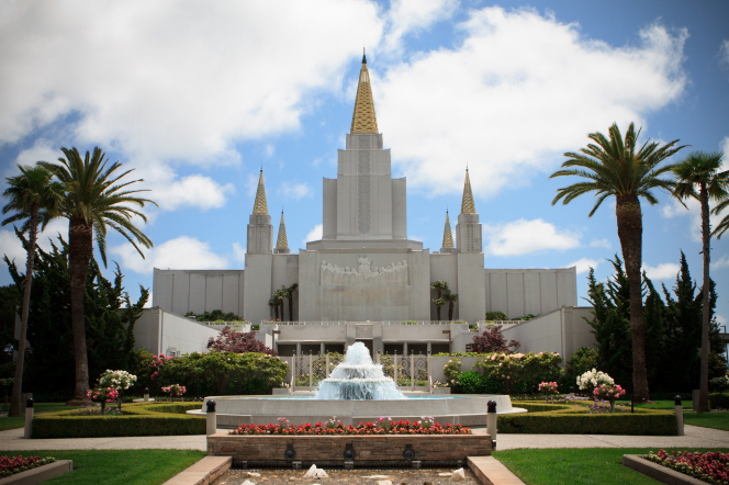 A view of the front of the Oakland California Temple, with palm trees and flowers growing on the grounds and a large water fountain in view.