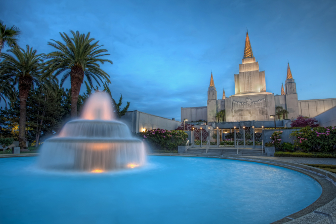 A water fountain on the grounds of the Oakland California Temple, with the temple seen lit up in the background during the evening.