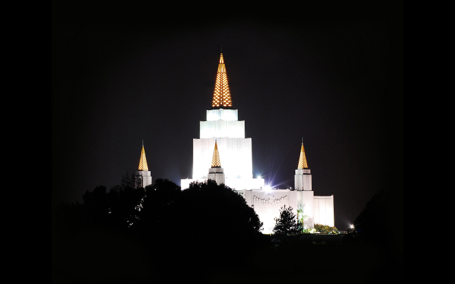 The spires of the Oakland California Temple lit up on a dark night, with darkened trees in the foreground.