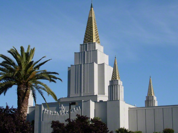 Three of the spires on the Oakland California Temple on a bright day, with a clear blue sky above and a large palm tree in the front.