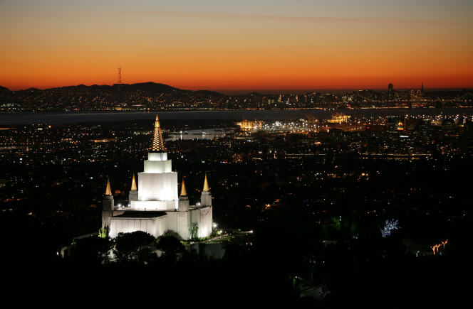 The Oakland California Temple illuminated in the evening, with the lights of the city showing in the background.