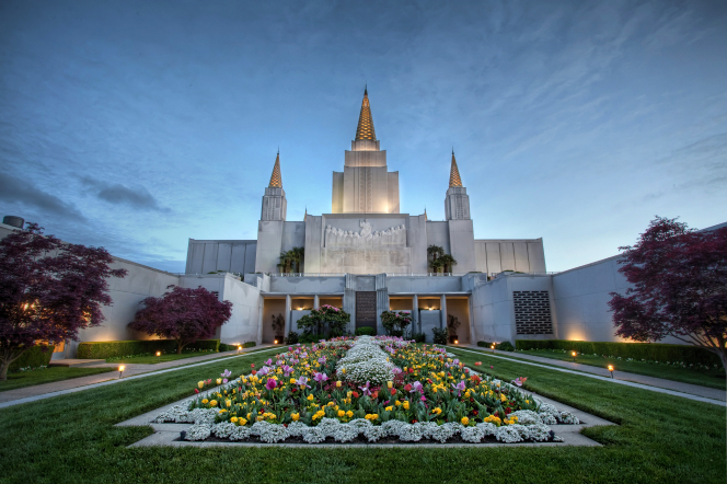 A wide-angle view of the Oakland California Temple in the evening, with flowers growing in a large flower bed on the lawn.