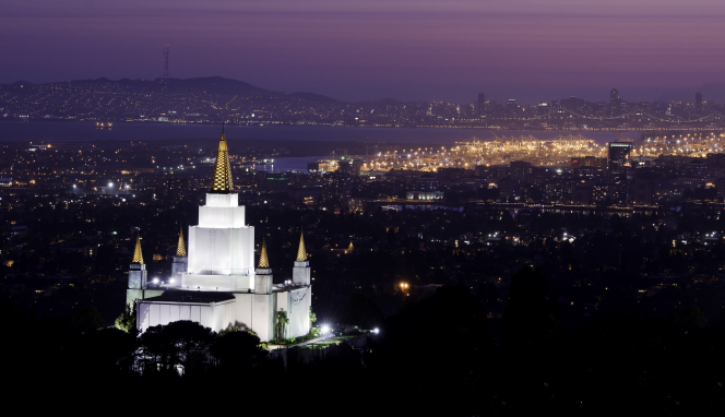 A view from afar of the Oakland California Temple, with the lights on in the evening and the glow of the city beyond.