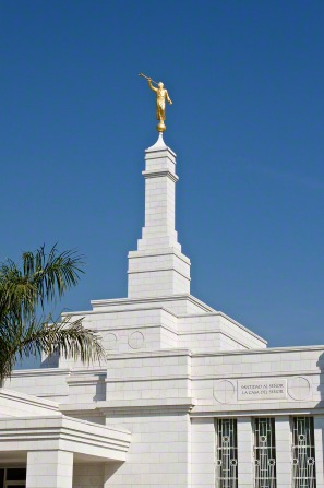 The front and spire of the Oaxaca Mexico Temple on a sunny day, with a bright blue sky overhead.