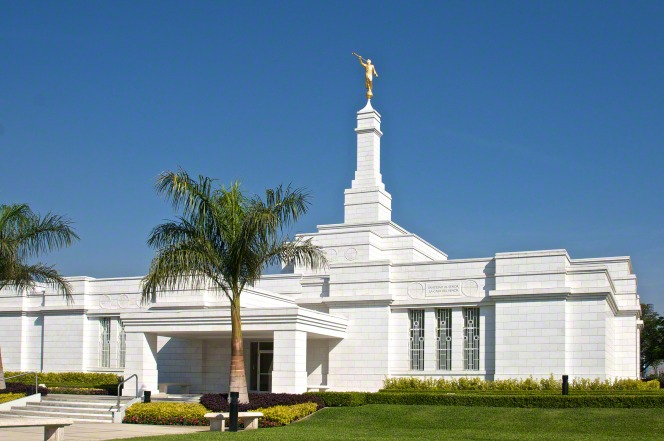 The front of the Oaxaca Mexico Temple on a warm day, with green lawns seen in the front on the right side.
