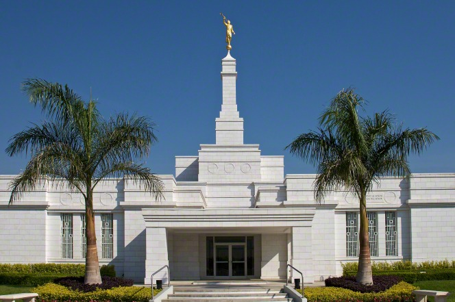 The front entrance to the Oaxaca Mexico Temple, with a clear blue sky overhead and two large palm trees near the doors.