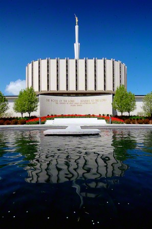 A pool of water on the grounds of the old Ogden Utah Temple, with the temple's sign in front of the temple, which is seen in the background.