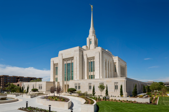 A front side view of the Ogden Utah Temple, with green lawns and some of the surrounding buildings on the street in the frame.