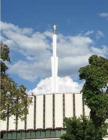 The spire of the old Ogden Utah Temple, seen between the green leaves of two large trees on the temple grounds.